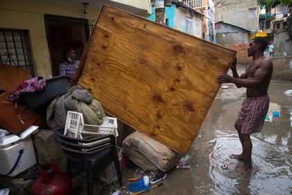Una pareja saca algunas de sus pertenencias a la calle para que se sequen luego de su hogar se inundara debido a las intensas lluvias causadas por Laura en Santo Domingo (República Dominicana) (EFE)