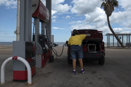 Una cliente carga combustible como parte de los preparativos para el huracán (AFP)