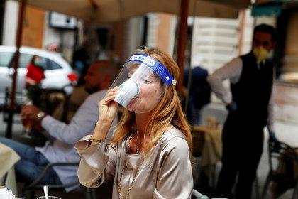 Una mujer con una máscara toma un café en un bar de Roma tras el levantamiento de las restricciones en mayo (REUTERS/Yara Nardi)