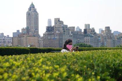 Una mujer revisa su teléfono en la nueva terraza de al Museo Metropolitano de Arte en su primer día de reapertura (Reuters)