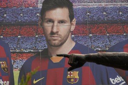 Vista de la estatua dedicada a Johan Cruyff con un cartel publicitario en el Camp Nou , días después de que el delantero argentino del FC Barcelona, Leo Messi, enviara un burofax al club catalán en el que solicita que se le conceda la carta de libertad para poder firmar por otro club.EFE/ Alejandro García