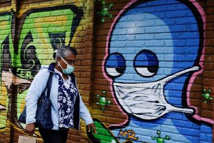 Imagen de archivo. Una mujer con mascarilla camina frente a un graffiti luego de que autoridades de salud revirtieran las medidas de reapertura tras el aumento de casos de coronavirus en San José, Costa Rica. 13 de julio de 2020. REUTERS/Juan Carlos Ulate