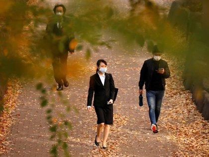 Transeúntes con mascarillas caminan bajo hojas de colores otoñales, en medio del brote de la enfermedad del coronavirus (COVID-19), en Tokio, Japón. 19 de noviembre de 2020. REUTERS/Issei Kato