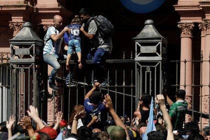 Fanáticos trepando las rejas de la Casa Rosada