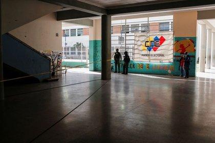 Miembros de la Guardia Nacional Bolivariana de Venezuela junto a una pancarta con el logo del Consejo Electoral de Venezuela en un colegio electoral durante las elecciones parlamentarias en Caracas, Venezuela, December 6, 2020. REUTERS/Manaure Quintero