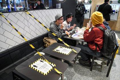 Jóvenes comen en un ambiente cerrado de un restaurante en la capital sueca (Reuters)