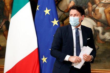 El primer ministro italiano Giuseppe Conte, con una máscara facial protectora, se retira al final de la conferencia de prensa de este viernes sobre las nuevas medidas contra el COVID-19 (REUTERS/Remo Casilli)
