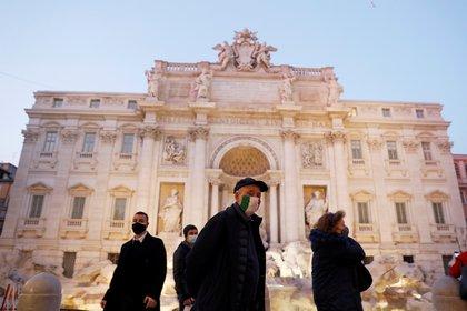 Italianos con máscaras faciales caminan frente a la Fontana di Trevi antes de Navidad bajo las restricciones por el COVID-19 en Roma el 17 de diciembre de 2020. REUTERS/Yara Nardi