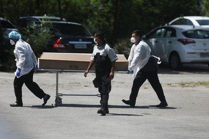 IMAGEN DE ARCHIVO. Trabajadores transportan fuera de un hospital público un ataúd que contiene el cuerpo de una persona que murió a causa del COVID-19, en Río de Janeiro, Brasil, Deciembre 18, 2020. REUTERS/Pilar Olivares