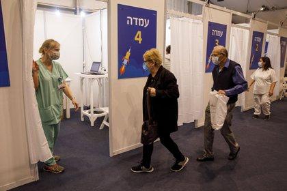 Una pareja de ancianos ingresa a un cubículo dentro de un centro de vacunación masiva contra el COVID-19 en la Plaza Rabin, en Tel Aviv, Israel (Bloomberg)