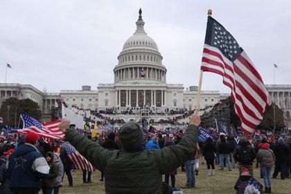 Un seguidor de Donald Trump sostiene la bandera de los Estados Unidos, el 6 enero de 2021, frente al Capitolio estadounidense, en Washington (Estados Unidos). EFE/MICHAEL REYNOLDS