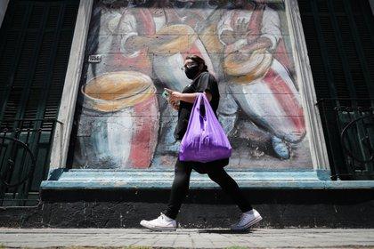 Una mujer pasa frente a un muro con un dibujo alusivo al candombe uruguayo, en Montevideo (Uruguay). EFE/Raúl Martínez/Archivo