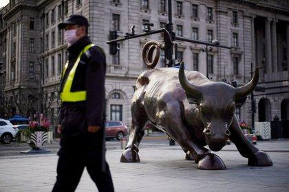 Un guardia de seguridad con una máscara pasa junto a una estatua del toro de Wall Street, luego del brote por la nueva enfermedad por coronavirus (COVID-19), en Shanghai, China. 18 de marzo de 2020. REUTERS/Aly Song