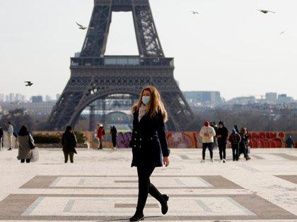Una mujer, con máscaras protectoras, camina frente a la torre Eiffel en el Trocadero de París en medio del brote de la enfermedad del coronavirus (COVID-19) en Francia, el 11 de febrero de 2021. REUTERS/Sarah Meyssonnier
