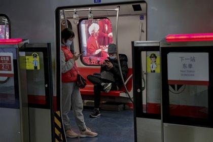 Viajeros con mascarillas leen en sus teléfonos celulares en el metro de Beijing, 10 de febrero de 2021. El organismo supervisor del internet en China obligará a los blogueros e influencers adquieran una licencia para poder publicar opiniones sobre ciertos temas. (AP Foto/Andy Wong)