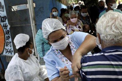 Una trabajadora de salud vacuna a un adulto mayor en Brasil (REUTERS/Ricardo Moraes)