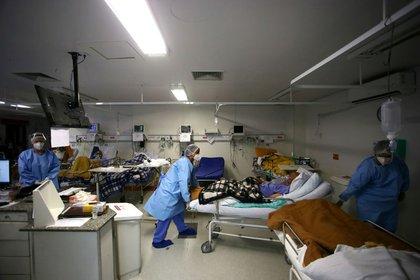 Trabajadores de la salud trasladan a un paciente de la sala de emergencias del hospital Nossa Senhora da Conceição en medio de la pandemia de coronavirus, en Porto Alegre, Brasil, Marzo 11, 2021 (REUTERS/Diego Vara)