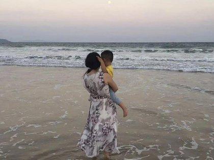 Zou Xiaoqi, una madre soltera convertida en activista en Shanghai, sostiene a su hijo mientras visitan una playa en Sanya, provincia de Hainan, en el sur de China (AP)