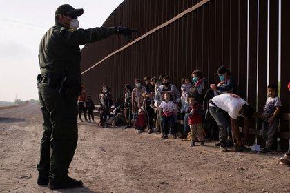 Un agente de la Patrulla Fronteriza de EEUU instruye a los migrantes solicitantes de asilo mientras se alinean a lo largo del muro fronterizo después de cruzar el río Grande hacia Estados Unidos desde México en una balsa, en Penitas, Texas, EEUU. 17 de marzo de 2021. REUTERS/Adrees Latif