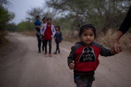 Taznari, una niña migrante hondureña solicitante de asilo de tres años, toma la mano de su madre mientras caminan por un camino de tierra después de cruzar el río Grande hacia Estados Unidos desde México en una balsa en Peñitas, Texas, Estados Unidos, marzo 16 de febrero de 2021 Foto: (REUTERS/Adrees Latif)