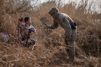 Un policía estatal de Texas pide a los inmigrantes en busca de asilo Edith y su hijo Harbin Ordóñez, de 4 años, que salgan de su escondite después de que los hondureños cruzaron el río Grande hacia los Estados Unidos desde México en una balsa en Peñitas, Texas, el 9 de marzo de 2021 Foto: (REUTERS/Adrees Latif)