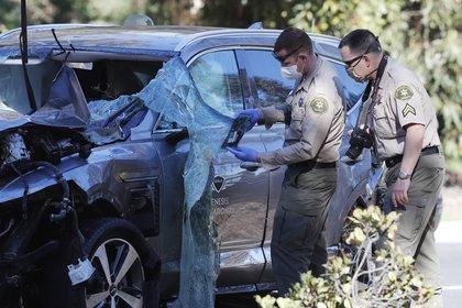 Agentes del condado de Los Ángeles examinan el auto SUV Genesis GV80 conducido por Tiger Woods, el 23 de febrero pasado. EFE/EPA/ETIENNE LAURENT/Archivo