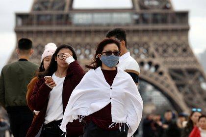 La Torre Eiffel es el marco de los transeúntes que caminan con mascarillas en parís (REUTERS/Gonzalo Fuentes)