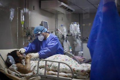 Un trabajador de la salud atiende a una paciente covid-19 en la Unidad de Cuidados Intensivos (UCI) del Hospital de Clínicas hoy, en San Lorenzo (Paraguay). EFE/Nathalia Aguilar