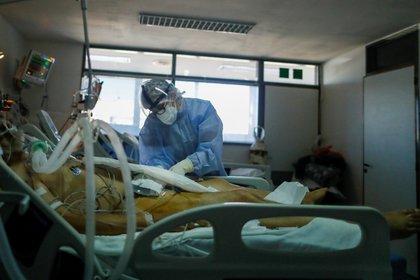 Un trabajador de la salud revisa a un paciente que padece la enfermedad del coronavirus (COVID-19), en una unidad de cuidados intensivos de un hospital en las afueras de Buenos Aires, Argentina, 16 de abril de 2021. Fotografía tomada a través de un cristal. REUTERS / Agustin Marcarian