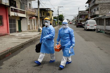 Médicos que forman parte de una unidad de rápida respuesta del Ministerio de Salud ecuatoriano caminan a una residencia en Guayaquil (REUTERS/Santiago Arcos)