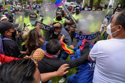 Manifestantes sostienen a un hombre al que acusan de ladrón durante una marcha en Quito, Ecuador 23 de febrero de 2021 (REUTERS/Santiago Arcos)