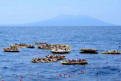 Flores y pétalos con los nombres de los miembros hundidos de la tripulación del submarino KRI Nanggala-402 se ven en el mar cerca de Labuhan Lalang, Bali, Indonesia (Reuters)