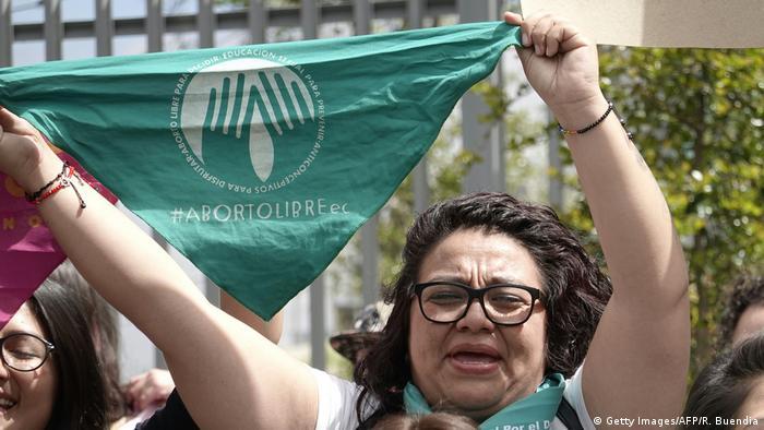 Foto de una mujer que protesta con un pañuelo verde que dice aborto libre en Ecuador