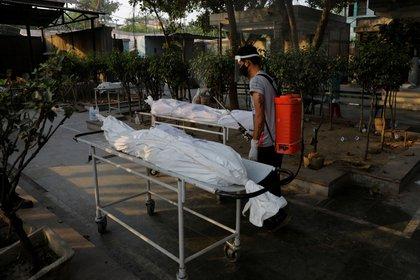 Un empleado municipal traslada los cuerpos de dos víctimas del coronavirus en un crematorio de Nueva Delhi (REUTERS/Adnan Abidi)