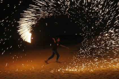 Un manifestante palestino sacude una antorcha en Gaza, cerca de la frontera con Israel, en un contexto de protestas / AFP PHOTO / SAID KHATIB