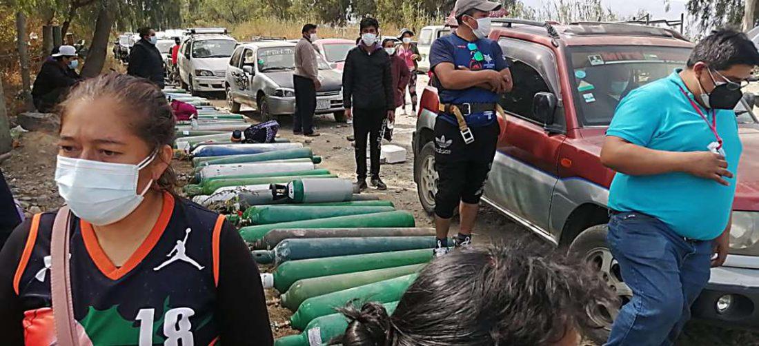 Varias personas duermen fuera de una planta de oxígeno para cargar sus cilindros