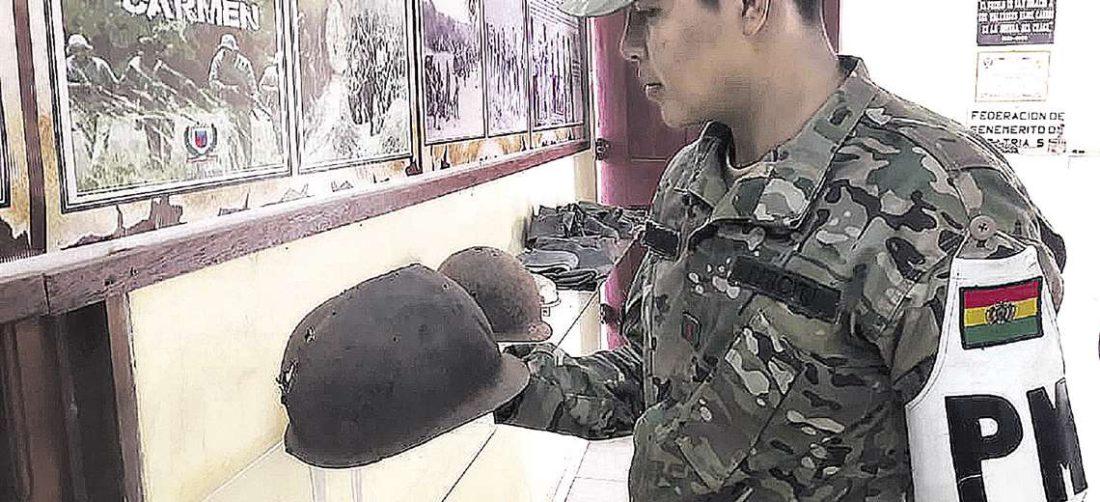 Un militar observa el casco utilizado por un benemérito en la guerra