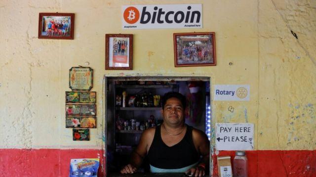 Un hombre de pie en su tienda que acepta bitcoins como pago.