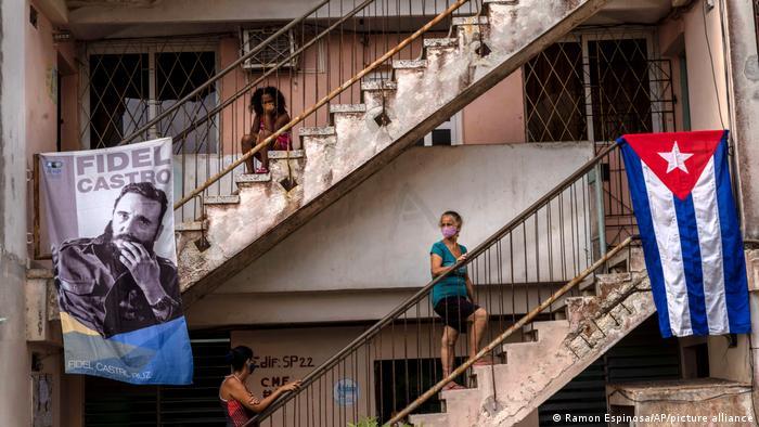 Personas hacen fila para ser vacunada con la vacuna Abdala en un consultorio médico, decorado con la imágen de Fidel Castro y la bandera cubana.