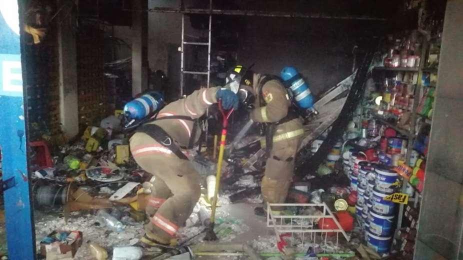 Bomberos de la policía sofocan el incendio en una ferretería. Foto: JC Torrejón