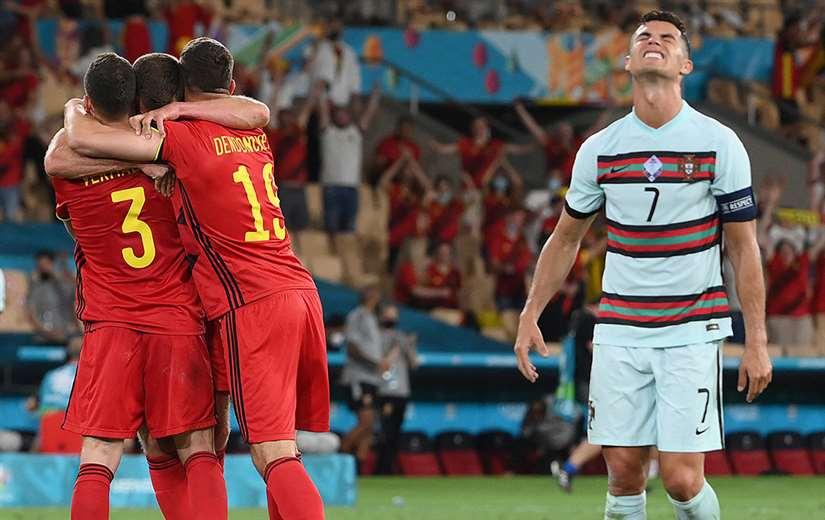 Bélgica festeja; mientras CR7 (izq.) lamenta la caída de su equipo. Foto: AFP