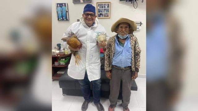 El médico y el adulto mayor después de obsequiar un par de gallinas. RRSS
