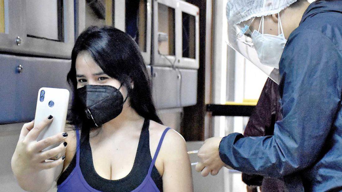 Una joven se toma un autorretrato mientras recibe la primera dosis de la vacuna. DICO SOLÍS