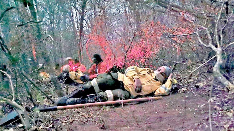 Bomberos voluntarios descansando en medio de las labores de mitigación del fuego. ANAHI PARAVICINI