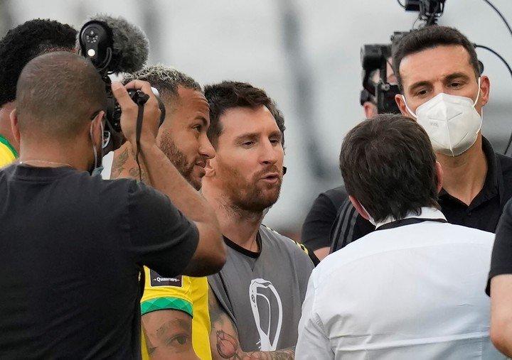Lionel Messi y Lionel Scaloni discuten con representantes locales tras la interrupcion de Brasil-Argentina. Foto AP