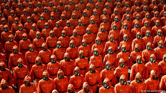 Personal con trajes anaranjados para materiales peligrosos marchan durante el desfile paramilitar.
