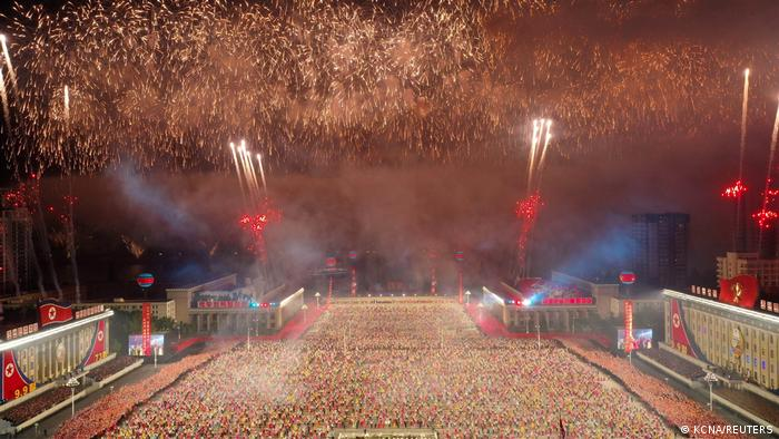 Fuegos artificiales explotan sobre un desfile paramilitar.