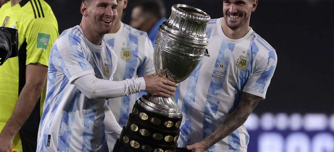 Messi sostiene el trofeo de la Copa América junto a De Paul. Foto: AFP