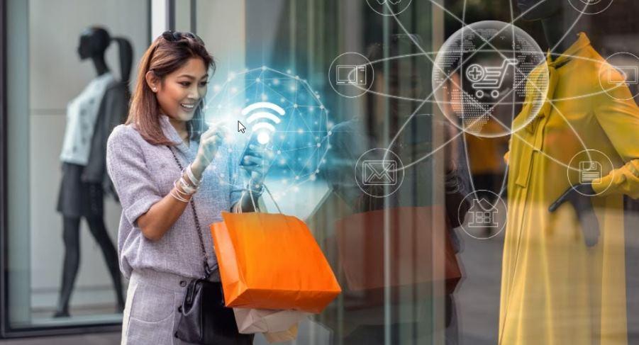 Omnicanalidad mostrada con una mujer comprando desde el móvil delante de una tienda