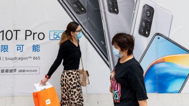 Una publicidad del teléfono Xiaomi 10T Procon dos mujeres que pasan caminando.